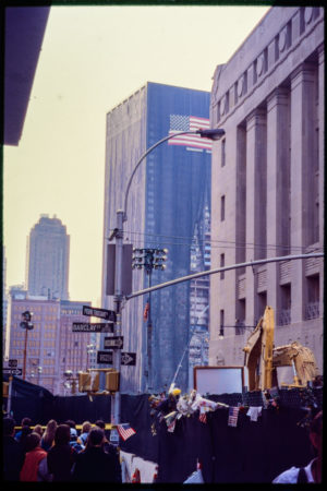 Pedestrians Watch Construction at the Corner of Barclay Street and Pierre Toussant Sqaure, Building Shrouded in the Background with the American Flag Near the Top.jpg