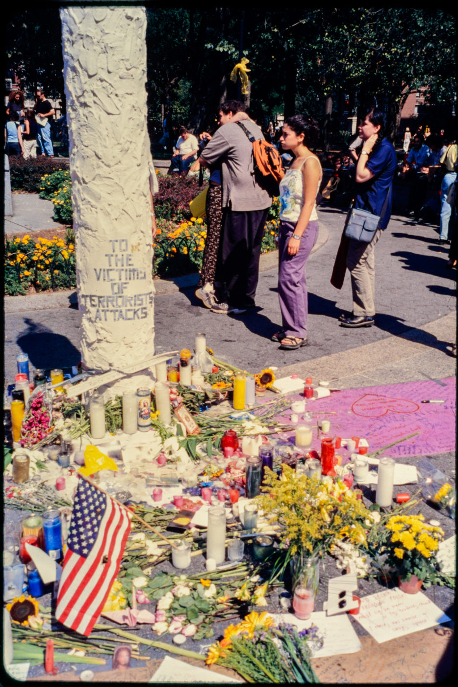 Two New Yorkers Embrace and Others Pass Near the Memorial at Union Square Park.jpg