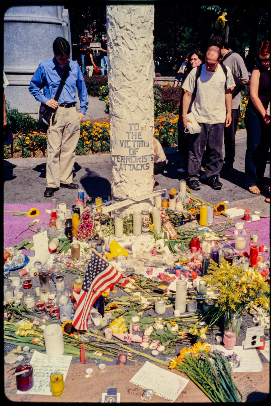 Two New Yorkers Stand on Opposite Sides of Memorial Structure, Overlooking the Messages Left for Victims of the Attack.jpg