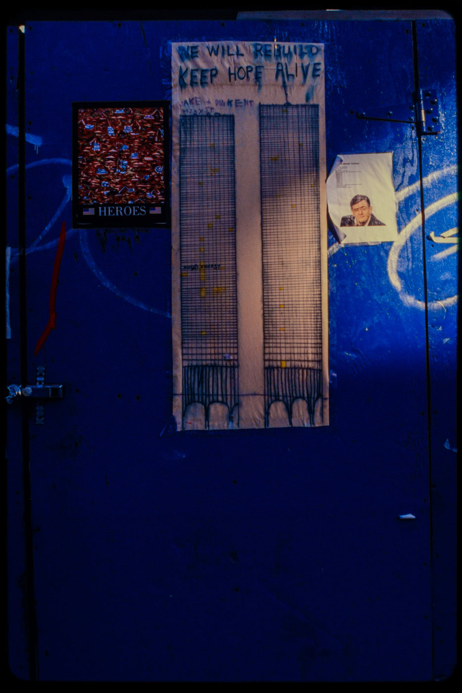 We Will Rebuild Keep Hope Alive Artwork with Other Flyers on Blue Door, Ray of Light Coming in From Right.jpg