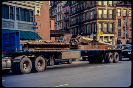 What Appears to Be Beams Are Fastened to a Flat Truck Near White Street.jpg