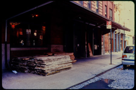 Wooden Boards Piled Up On the Sidewalk by a Cobblestoned Road.jpg