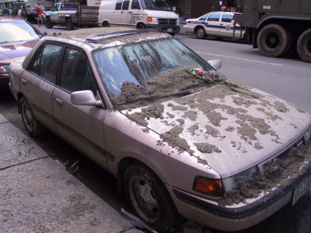 Dust and Dirt All Pver a Car with a Flower Someone Has Laid on the Car.JPG
