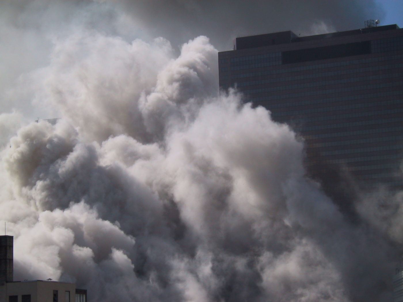 Thick Smoke Covering the Ground and Surrounds the Buildings as the Towers Collapse.JPG