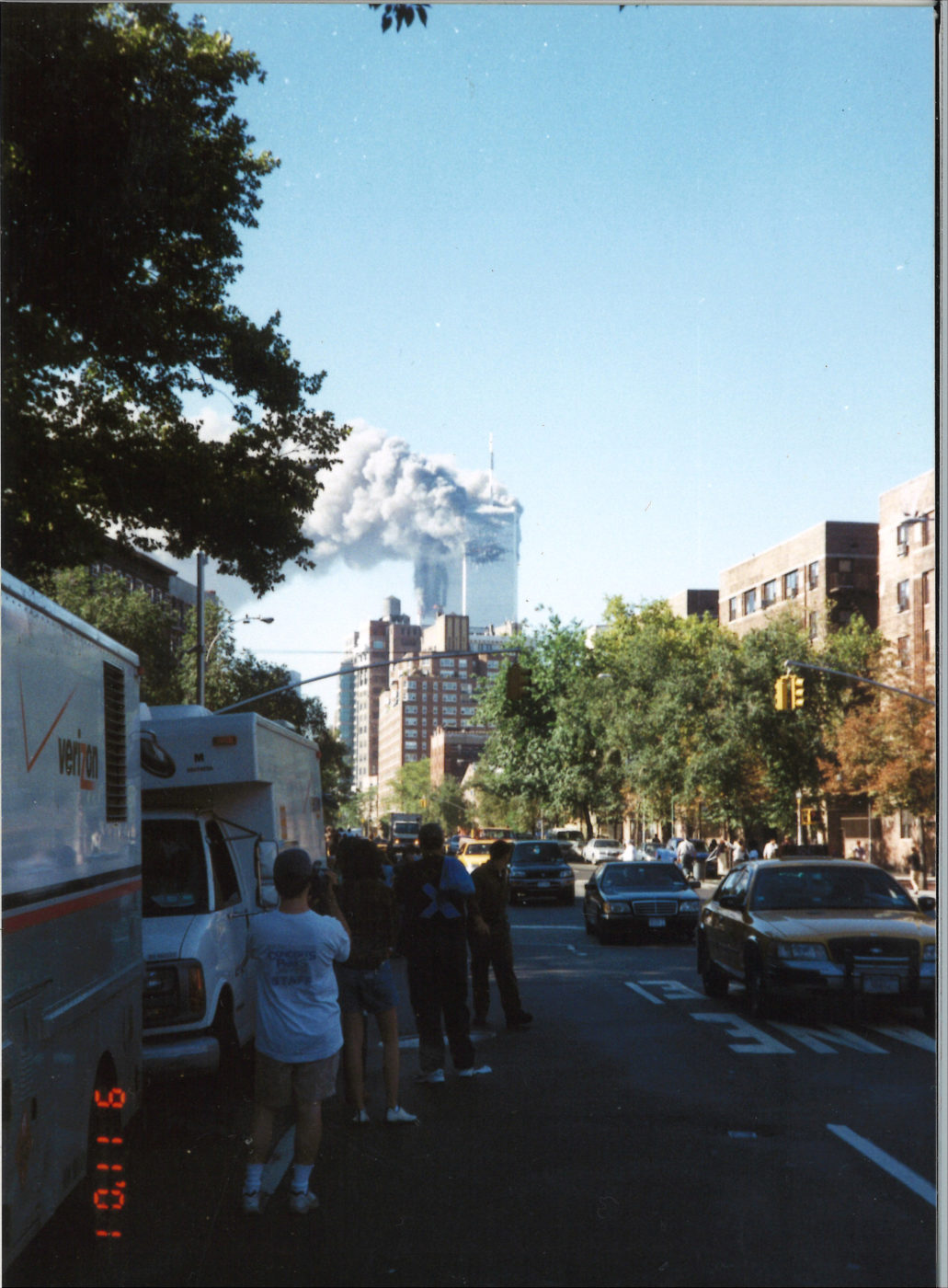 New Yorkers Stand Alongside Traffic Watching the Towers on Fire Looking South From Bleecker Street and 6th Avenue vertical view.jpg