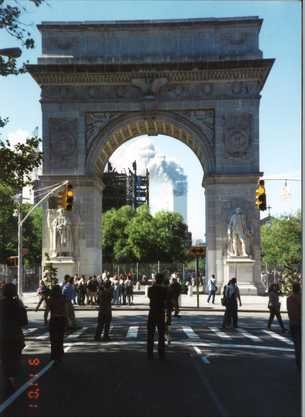New Yorkers Stand Together Shocked Tower Looking Through the Arch Looking Down 5th Avenue 1 Burning after Collapse of Tower 2.jpg